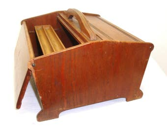 Wood sewing box. Double top doors hinge open to large interior, sliding accessory tray for spools etc. Some wood loss, nicks, scratches