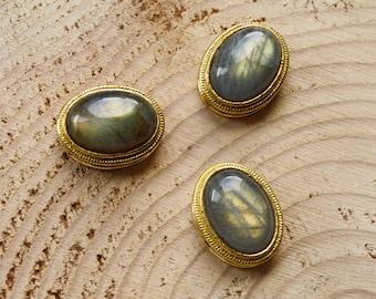 Grooved oval gold flash labradorite cabochon set in brass. High grade, 23 ct crystal semi precious gemstone