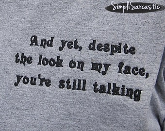 T-Shirt:  And yet, despite the look on my face, you're still talking.  - Light Gray, Unisex, sarcastic shirt, funny shirt, gag gift