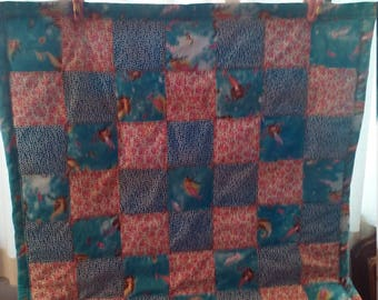 Mermaids and jellyfish swim across this sweet little baby quilt