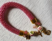 Pink Beaded Bracelet with porcelain, glass beads, and a small butterfly pendant. Beaded crochet rope
