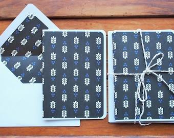 Minimalist leaf design on black paper card and envelope set