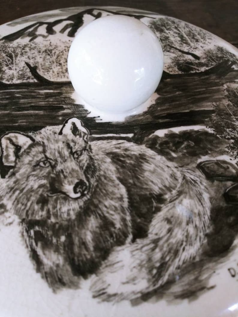 Vintage Mid Century Alaskan Art by Bering Sea Originals featuring a Wolf in a woodland scene on a round ceramic covered trinket box