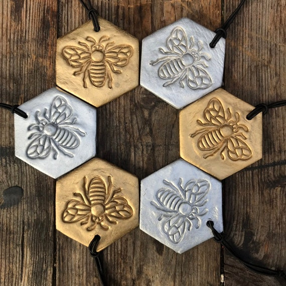 BEE CHRISTMAS DECORATION : A Manchester Bee xmas decoration. Available in Gold or Silver.