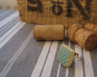 Scrabble tile with blue and yellow dots ring
