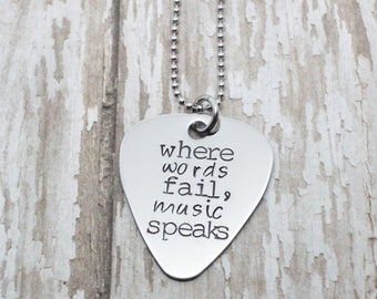 """hand stamped guitar pick necklace """"where words fail, music speaks"""""""