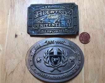 Alcatraz penitentiary and Phat farm belt buckles . Both damaged . Pins missing . Good collectible condition