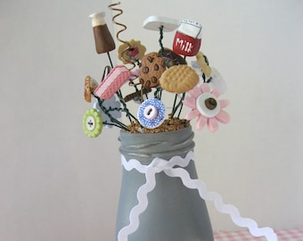 Cookies and Milk Button Bouquet arranged in a decorative milk bottle.  Cookie  and flower buttons along with a bottle and carton of milk.