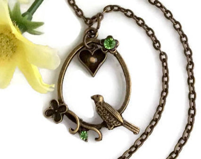 Antique bronze pendant with bird, heart, green rhinestone flowers and real mustard seed set in heart.  Faith of a mustard seed necklace.