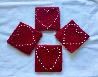 Red felted wool coasters with embroidered heart design