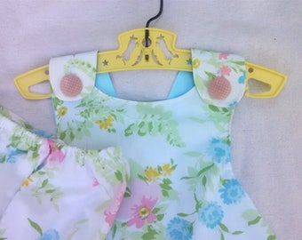 Reversible sundress with pastel floral pattern on one side & coordinating sky blue on the other. Vintage buttons. Panties, too. Size 2T.