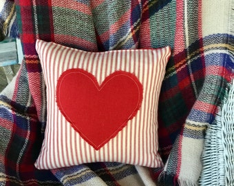 Pillow cover features red ticking stripe fabric with red linen heart appliqué