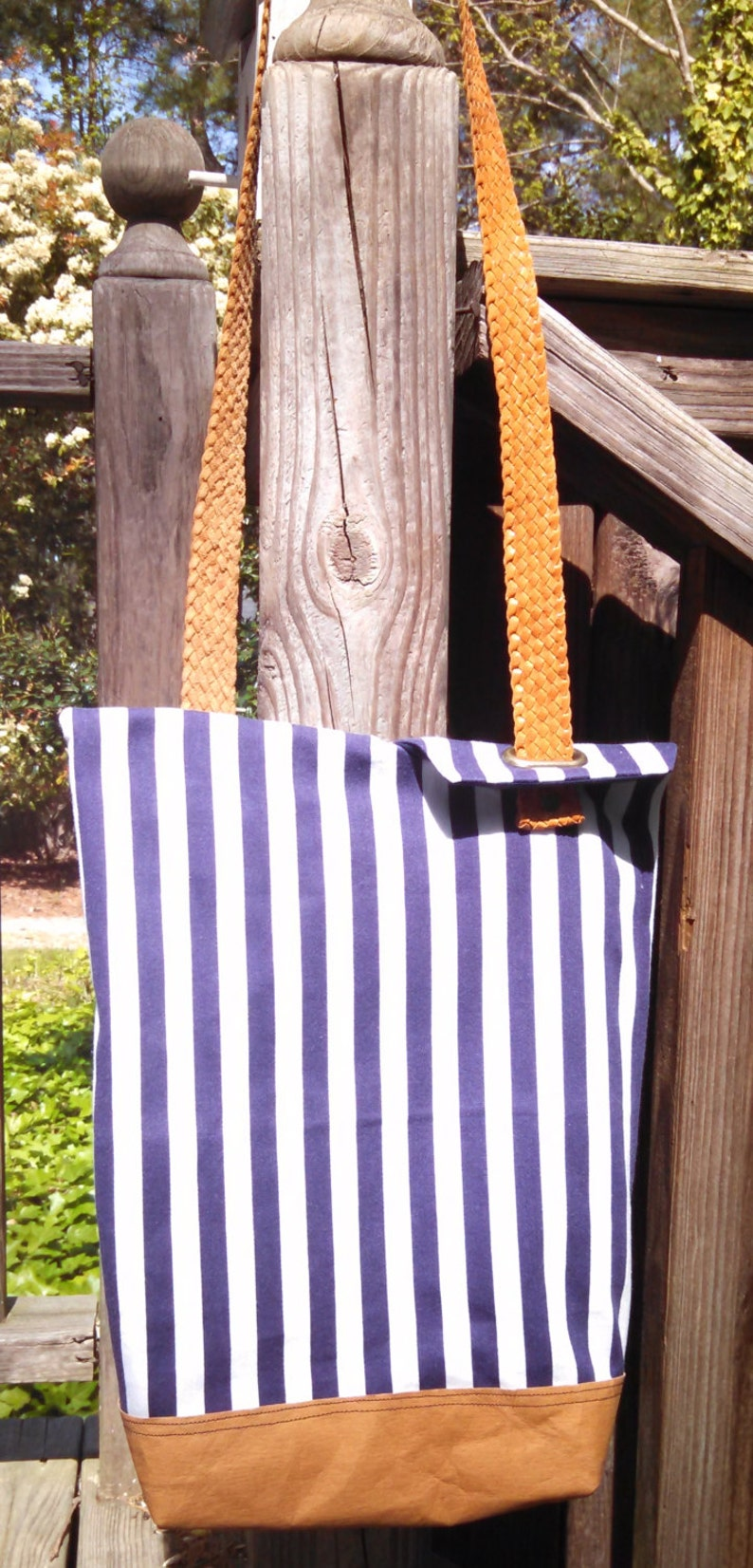 So sharp in navy and white stripes This totepurse has one leather strap that is unique and holds the flaps closed when purse is held.