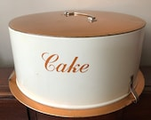 Vintage cake carrier, light weight metal cake carrier with clips at base to secure the top. Copper and cream color. Retro.