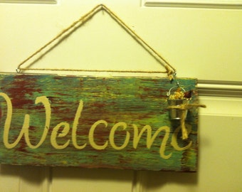 Welcome sign with metal pail and flowers