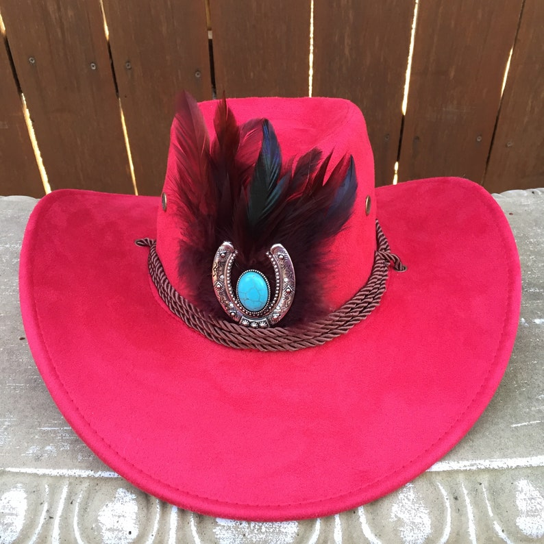 6b916a3ce Red Cowboy Hat with Brown Feathers and a Horseshoe with Turquoise Colored  Stone Medallion and a Brown Rope Hat Band with Chin Strap