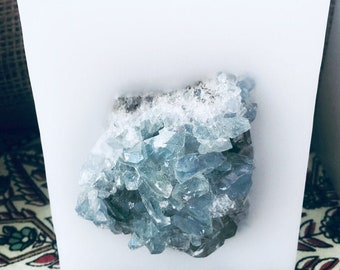 Crystal Candle~ White Chub Square Candle with an inlaid Blue Celestine Crystal Cluster that illuminates when lit! Burns for 200 hours