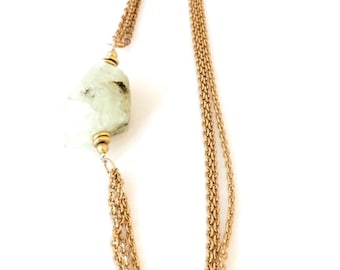Prehnite gemstone necklace sitting asymmetrically with multiple strands of raw brass chain