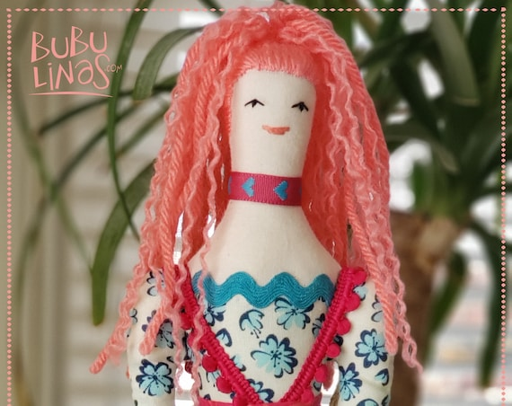 rag doll with coral pink hair and pink dress with teal blue leggings