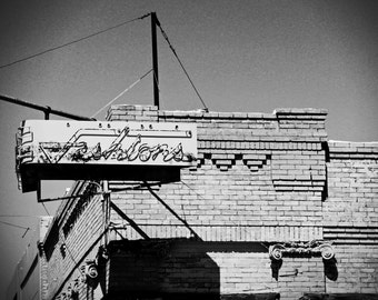 Vintage fashion sign, black and white photograph, fine art photography, old photo, antique sign, brick building