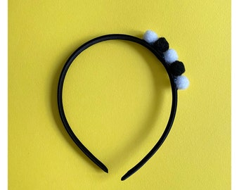 Headband with soft colored pompoms