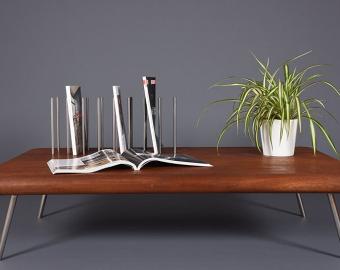 Modern coffee table made of solid mahogany wood with legs and magazine rack in solid steel