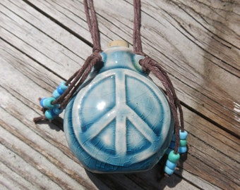 Peace Sign Bottle Necklace, Blue ceramic raku bottle on Brown Hemp with smaller matching peace sign beads and glass accent beads.