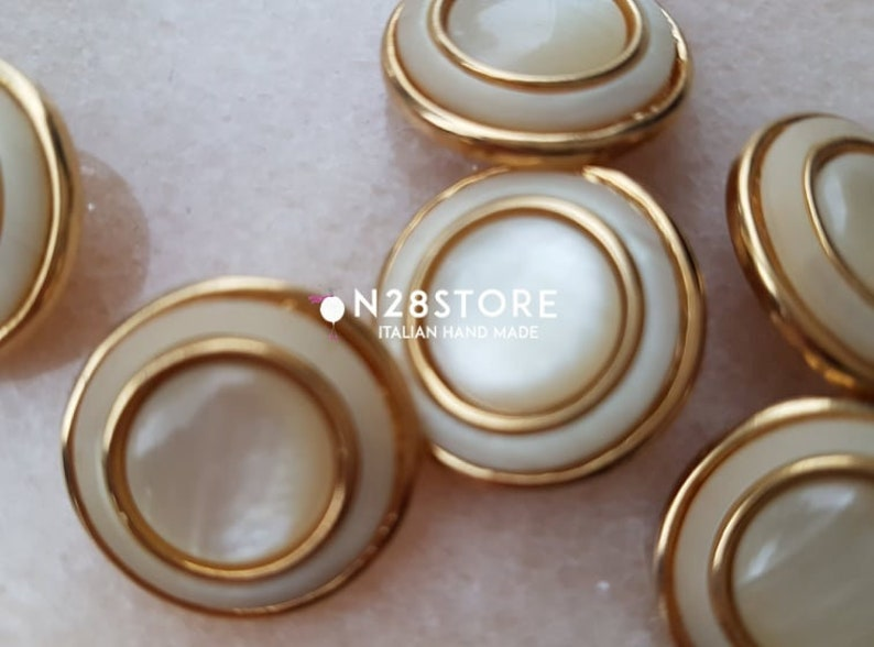 measuring 20 mm. Beautiful shank buttons available in gold and ivory mother-of-pearl