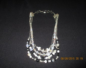 "Multi strand  22"" necklace with black, white,crystal beads and embellishments with silvertone clasp"