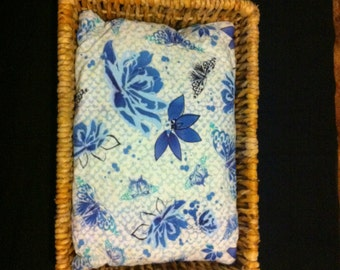 Butterflies and flowers print pillow in a wicker basket