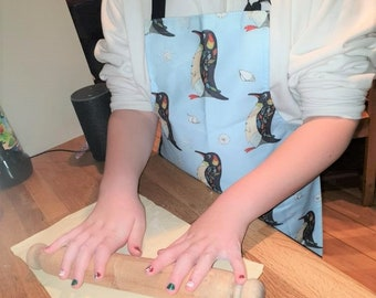 Stanley penguin child's sized apron. Printed cotton apron from an original embroidery by Sarah Ames