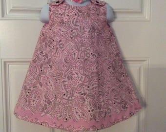 07561a1b6 A-line baby dress in a beautiful paisley pink fabric, embellishments  include zigzag trim and stretchy headband with a pink fabric rose.