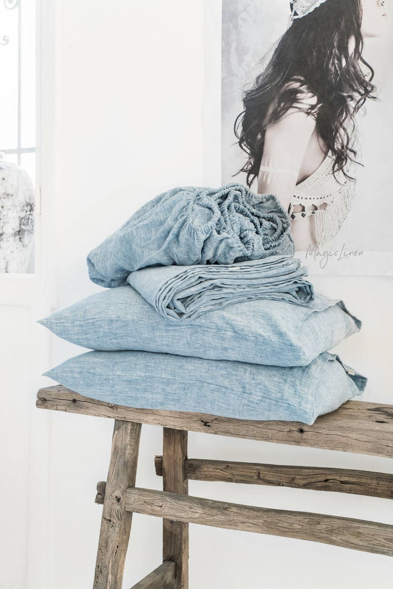 Rustic raw wood bench piled with beautiful chambray linen bedding - beachy serene indeed!