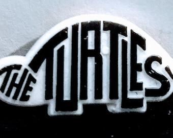 "The Turtles (Flo & Eddie), Pinback/Lapel Pin! Authentic Vintage 1990! The Turtles Pinback, High Impact Plastic! 1 5/58""Long X 1/2""High!"