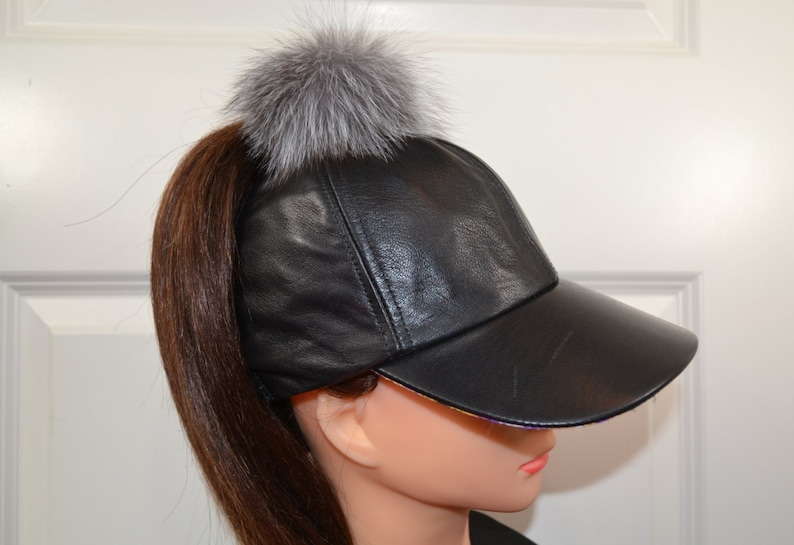 fe9403cf852 Black leather women s baseball cap with a real fur pompom