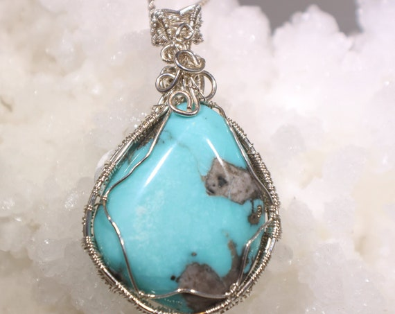 Beautiful Blue New Mexico Turquoise with fools gold inclusions wrapped in sterling silver wire.