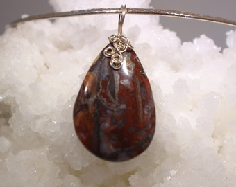 Pietersite cabochon pendant is very bright.  It is predominantly red.  Chatoyant Very simple gold filled wire bail.  2.5 in overall length.