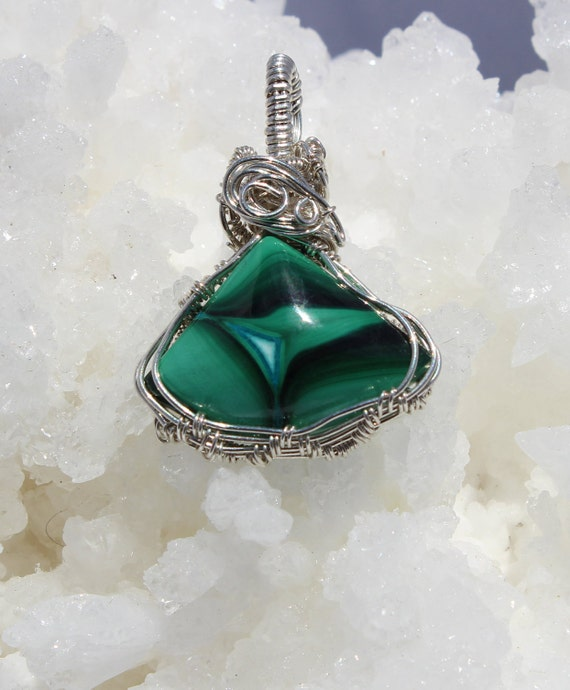 The unusual cut of this Malachite stone invites and enhances imagination, bold colors wrapped in Sterling Silver,   18 in. silver chain