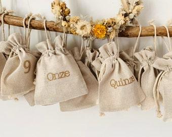 Advent calendar in reusable fabric, natural linen color. Figures in golden glitter. 24 sachets.