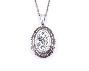 Antique engraved locket, silver with floral engraving.