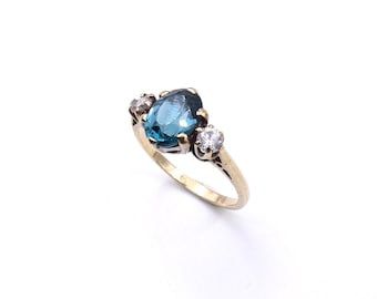 Vintage blue topaz ring, three stone vintage ring in 9kt gold with zirconias and a central teal gemstone.