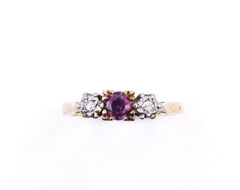 A ruby diamond three stone vintage ring in 18kt gold.