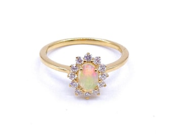 An opal and diamond cluster ring set in 18kt gold.
