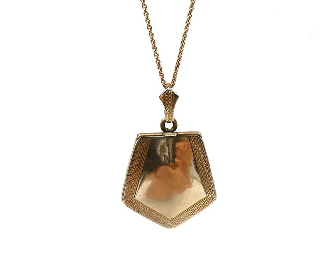 Vintage gold locket, art deco style locket in a shield shape with a patterned border.