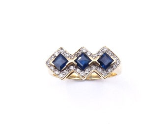 Vintage sapphire ring in an Art Deco style, a three stone sapphire ring surrounded by diamonds in a geometric design.
