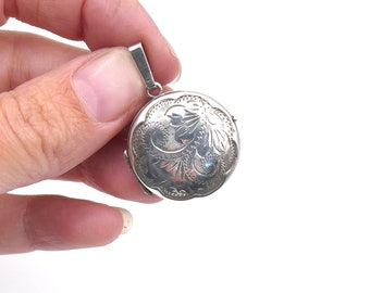 Vintage silver round locket with a scalloped border and leaf motifs, on a fine silver chain.