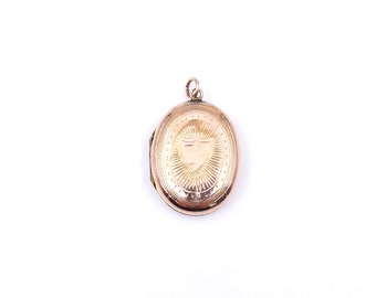 Antique rose gold locket in an oval shape, engraved rose gold locket with a shield design.