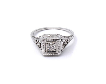 Antique diamond ring, an art deco 18kt white gold ring with a diamond and an ornate engraved setting .