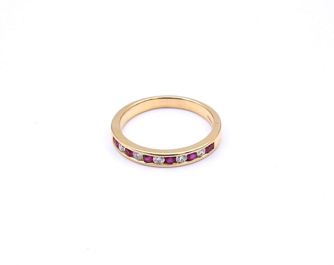 A ruby and diamond eternity ring in 18 carat gold