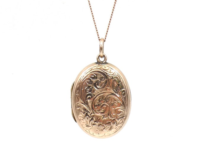 Engraved rose gold locket, an oval rose gold victorian back and front locket with floral and leaf motif.
